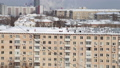Cleaning the roof from snow in a residential area of Moscow on a sunny winter day after heavy snowfall, Russia  74835633