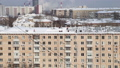 Cleaning the roof from snow in a residential area of Moscow on a sunny winter day after heavy snowfall, Russia  74835635