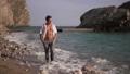 Muscular man walking on the beach 74852123