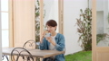 A woman watching a smartphone at a cafe 75005051
