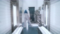 a production worker in a special uniform disinfects his hands 75012410
