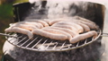 Sausages roasting on barbecue grill, outdoors. BBQ. Grilled food fried and smoked in charcoal grills. Turns the grill over with tasty delicious sausages 75040760