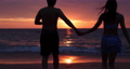 A teenage woman is running with her boyfriend on a beach with the sea and the golden sun in the evening. Concept pictures about love, romance, Valentine, propose. 4K. 75138172