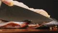 Chef cuts fins of raw red fish to prepare dish on board 75186128