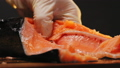 Chef in gloves cuts red fish into pieces with sharp knife 75191533