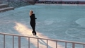 Young woman skates on a frozen lake outdoors 75209790