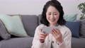 打電話的微笑的資深婦女在她的智能手機 75276481