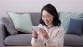 打電話的微笑的資深婦女在她的智能手機 75276482