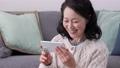 在她的60多歲,在她的智能手機上進行視頻通話的微笑的女人 75276484