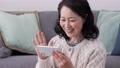 一個微笑的女人在向她的智能手機揮舞著她的60多歲的視頻通話圖像 75276485