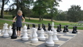 Little girl is playing large outside chess in the park. Active child, happy childhood concepts 75302823