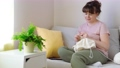 Young woman knitting white knitwear on sofa at home 75337788
