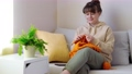 Young woman knitting orange knitwear on sofa at home 75337789
