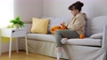 Young woman knitting on sofa at home 75337791