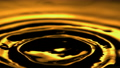 Ripples on the Surface of Golden Liquid Oil with Waves Creating Abstract Background Shot in Slow Motion 75338183
