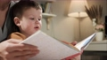 Baby and book. Side view of face of 2-3 year old baby who sits with his mother on bed in bedroom, female hands hold book and boy looks at it or reading it carefully. Slow motion 75360060