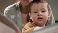 Mother and baby reading book. Front view of face of 2-3 year old baby who sits with his mother on bed, female hands hold book and boy looks at it or reads it carefully. Slow motion and close-up 75360061
