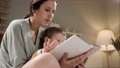 Baby and book, mother and child reading. Woman mom and 2-3 year old boy sit on bed in pajamas in bedroom in evening or night and hold book in hands, looking and reading, turn page. Slow motion 75360062