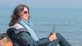 Woman sitting on the rock beach with laptop and enjoying spring sun 75405062