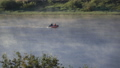 Fishermen Riding on Motor Boat along Foggy Morning River 75418886