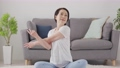 Senior woman stretching in the living room at home 75489292
