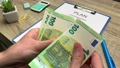 Concept of savings, man counts 100 euro banknote to start his own business. 75504446