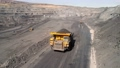 Large quarry dump truck. Loading rock in dumper. Loading coal into truck. Mining car machinery to transport coal. Open pit mine quarrying extractive industry stripping work. Big Yellow Mining Trucks 75529951
