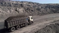 Aerial survey of truck. Dump truck carrying coal along in coal mine. Truck moving on dirt country road. Truck is driving along echnological road. Transportation of coal in trucks on road in open mine 75529952