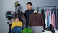 man selling hat and clothes online by camera live streaming, business online e-commerce  75590300