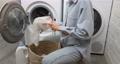Woman puts clothes into a laundry bag 75668911