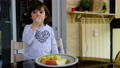 child eats a wedge-cut apple in the porch of the house. apples are a healthy food in the diet 75693461