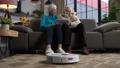 Robot vacuum cleaner working while elders relaxing 75707594