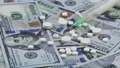 Medicines and syringe on the US dollars 75729300