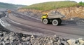 Large quarry dump truck. Loading rock in dumper. Loading coal into truck. Mining car machinery to transport coal. Open pit mine quarrying extractive industry stripping work. Big Yellow Mining Trucks 75736444
