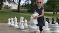 Little girl is playing large outside chess in the park. Active child, happy childhood concepts 75744476