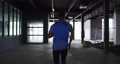 African american man wearing sports clothing jogging through an empty urban building 75870051