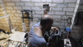 Adult mechanic repairing motor of motorcycle using hammer at garage. Male repairman doing his job at workplace. Professional repairer working at workshop. Concept of maintenance service. Dolly shot 75908784
