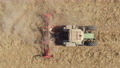 Aerial: Footage of Tractor with blades cutting up dry leftovers from a harvest to prepare the field before fertilizing and seeding. Farming equipment. sign visible at times says oversized load. 75911475