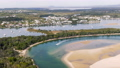 Aerial: Footage of Noosa lagoon with beautiful clear emerald water that flows down from the larger estuary system into the beach. Queensland, Australia. 75911808