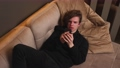 Annoyed young man holding smartphone frustrated by bad message, lying on sofa at home. 75937078