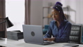 afro-american woman is working with laptop, remote job at home, young lady is sitting at table and 75976524