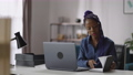 black businesswoman is working in home office, writing to do list in notebook, sitting at table with 75976970