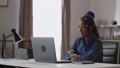 portrait of young black woman with purple dreadlocks at table with laptop, african american lady is 75976974