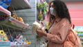 shopping at pandemic, woman with face mask is choosing toys in children store 76015616