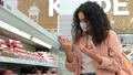 female customer with face mask is choosing sausage in grocery 76015647
