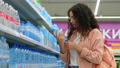 Woman buying mineral water in the supermarket 76015659