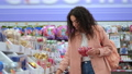 young brunette woman is buying Christmas decorations in supermarket 76015675