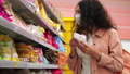 young lady is shopping in supermarket, wearing face mask, reading label on sweets 76015676
