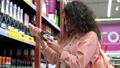shopping in alcohol department in supermarket, woman is choosing champagne 76015677