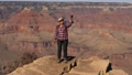 Hiker Woman Takes Selfie On Her Phone Standing On Edge Of Cliff In Grand Canyon 76039297